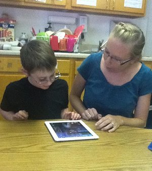 Teacher and student sitting at a table and using an iPad2