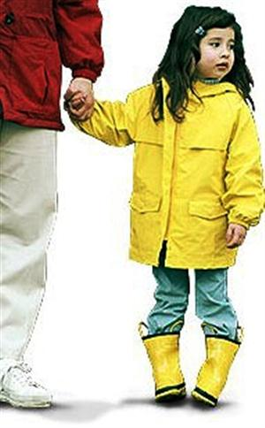 Child holding hands wearing yellow raincoat and boots.