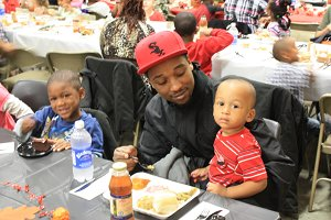 Dad with son on lap eating Thanksgiving meal at Harris Elementary
